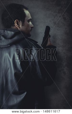 Man armed with gun on black textured background