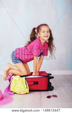 happy little girl collect the suitcase. The concept of travel and lifestyle.