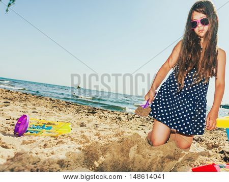 Having fun and joy concept. Little lovely gorgeous long haired girl playing with sea sand. Playful active kid on beach in summer vacation.