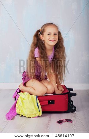 happy child with very long hair near a suitcase