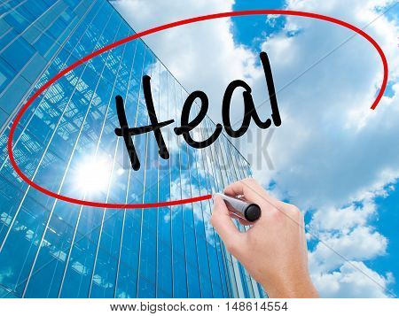 Man Hand Writing  Heal  With Black Marker On Visual Screen