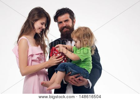 young happy family of handsome bearded man father pretty smiling woman with long hair and blonde child little boy playing with bear toy and red present box isolated on white background