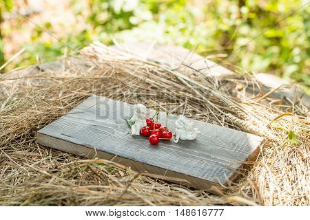 wild berry of fresh natural healthy red cherry with green leaves on wooden board and straw or hay with angel valentine figures