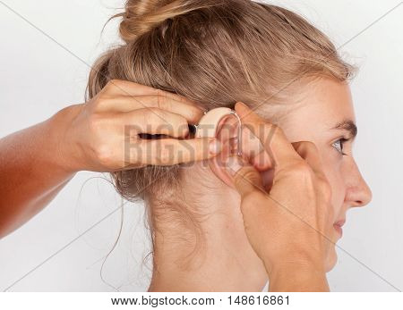 Close up of hands inserting a hearing aid in the ear of a young woman