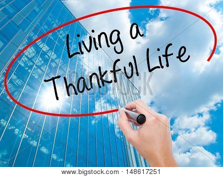 Man Hand Writing Living A Thankful Life With Black Marker On Visual Screen