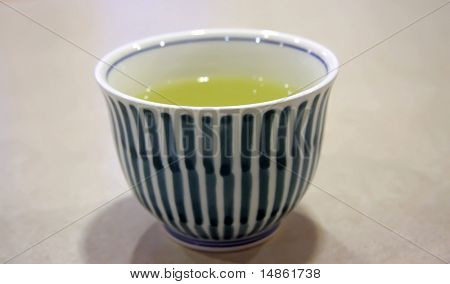 Bowl of green tea in white blue bowl traditional japanese beverage