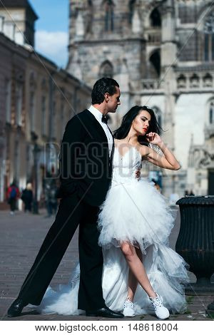 young wedding couple of sexy girl with brunette hair and pretty face in white bride dress and handsome man in black groom suit standing near castle or palace building sunny outdoor