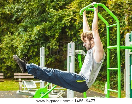Strong active man in training suit exercising working out at outdoor gym. Sport fitness concept.