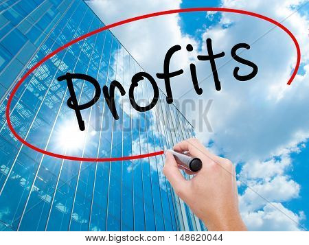 Man Hand Writing Profits With Black Marker On Visual Screen.