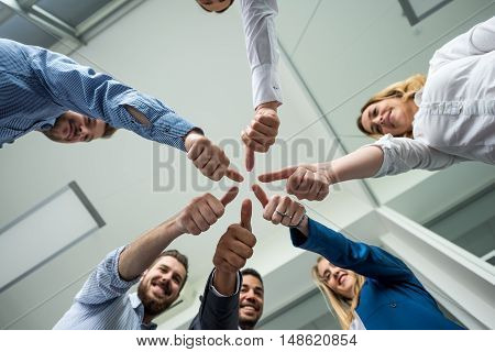 Businesspeople showing thumbs up in an offiice.
