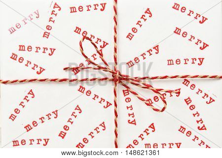 Closeup of a christmas present wrapped with white paper and twine and the word Merry randomly stamped on the paper.