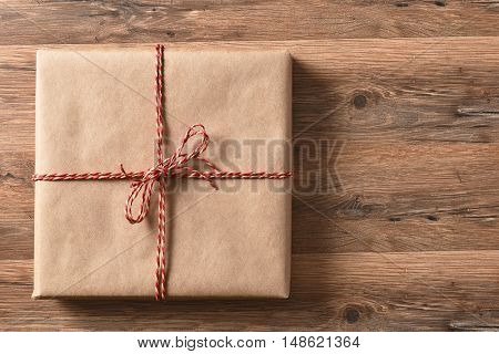 High angle view of a plain paper wrapped present on a rustic wood table.
