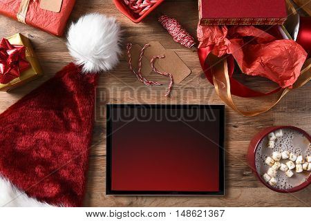 Christmas Presents, Tablet Computer, Santa Hat and Cocoa on a wood table.