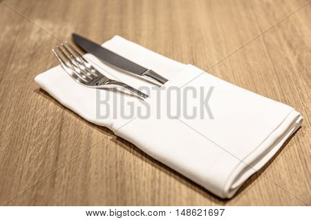 Fork And Knife Lie On A Folded White Napkin In The Restaurant.