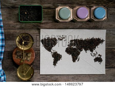map of the world, lined with tea leaves on old paper. vintage. green tea, a towel, scales, weights on rustic wooden table. top view. flat lay