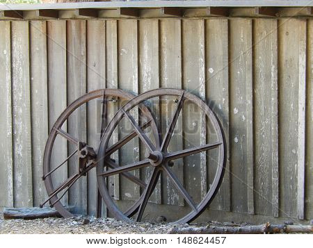 two wagon wheels leaned against a shed