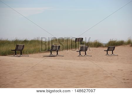 A group of park benches on the beach of Frankfort, Michigan