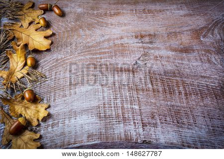 Border of oat acorn and fall leaves on the old wooden background. Thanksgiving background with seasonal symbols.