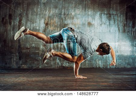 Young strong man break dancing on old wall background