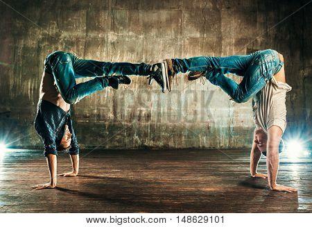 Break dancers team in old urban interior on wall background