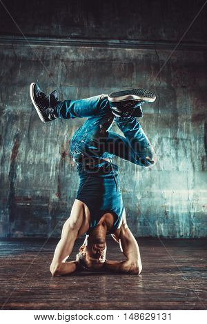 Young man break dancing on old wall background. Vintage film style colors.