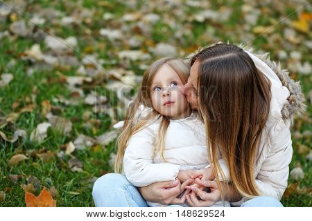 Family walk. Mother hugs and kisses daughter. Autumn Park. Cute family relationships.