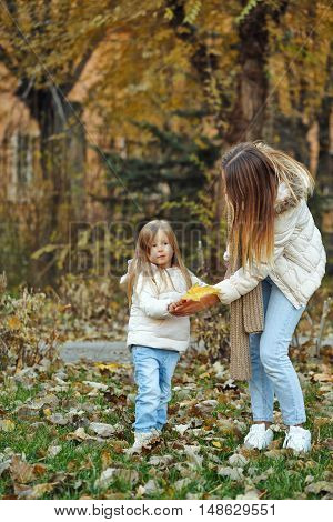 Family walk. Mother and daughter. Fallen leaves. Autumn Park. Cute family relationships.
