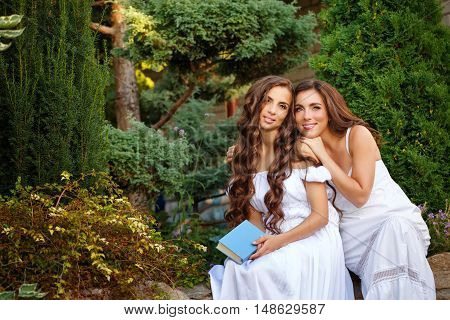 Two sisters. She holding a book and sister hugging her. Girls in long white dresses. Family time in the backyard.