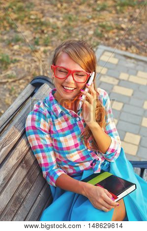 Young attractive woman holding a notebook and talking on the phone while sitting on a park bench. Hipsters and sketchbooks.