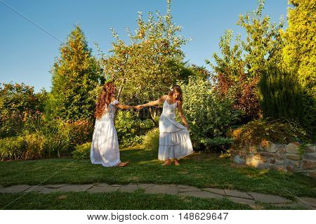 Two sisters. Girls whirling barefoot on the green lawn in long white dresses. Family time. Human relationships.