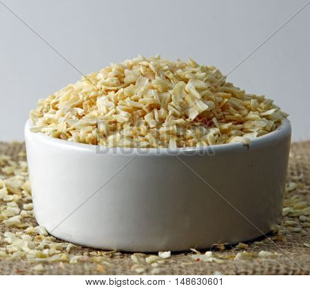 Dried Onion flakes in a bowl on a burlap cloth selective focus