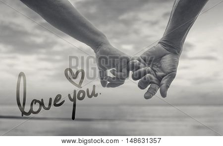 close up hand of senior couple hook each other's little finger together near seaside at the beach,black and white picture color,selective focus,love forever concept,text love you