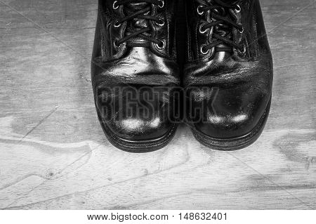 old black combat boots on wooden backgroundblack and white tone
