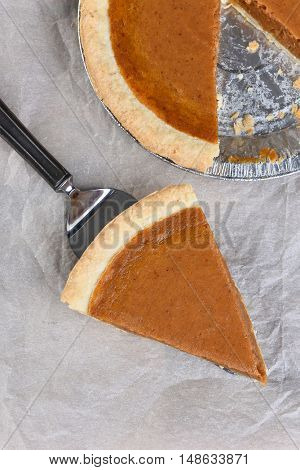 Fresh Baked Pumpkin Pie slice on a server. High angle shot with the rest of the pie in the background.