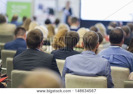 Professional Female Host Speaking in Front of the Large Audience During Business Conference. Horizontal Image