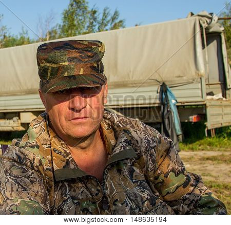 Portrait of a fisherman in camouflage uniforms at dawn