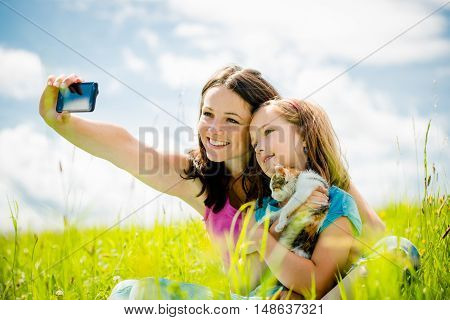 Mother taking photo with her smart-phone camera of herself, her girl and kitten - outdoor in nature