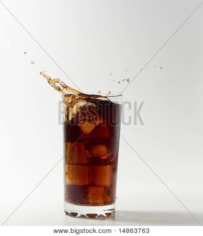 Ice cube droped in cola glass
