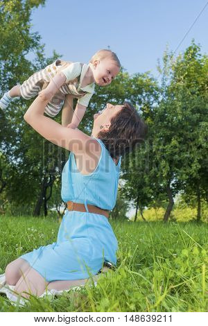Happy Mother Tossing Up Her Kid While Playing with Him in Park Outdoors. Vertical Image