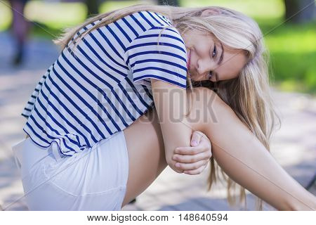 Pretty Blond Teenage Girl in Striped Shirt Posing With Smile Outdoors in Park Area. Horizontal Image Orientation