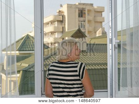 Waist Up Back Portrait Of Aged Woman Near Window.