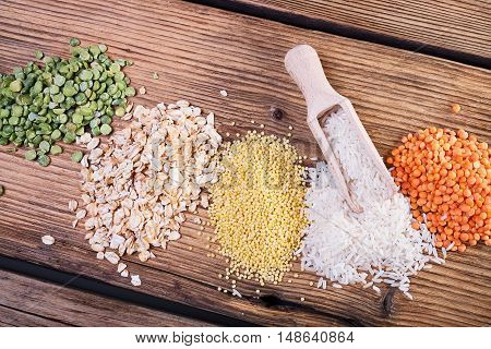 Krupa scoop, wooden spoon, an assortment of cereals, a table of old wood, the grain harvest, organic food, the texture of old wood, kitchen utensils, health food, scattering grains