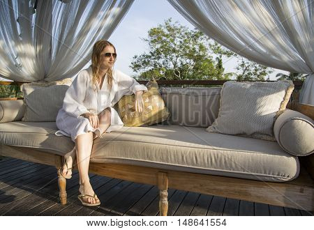 young woman in a bathrobe resting in a shade