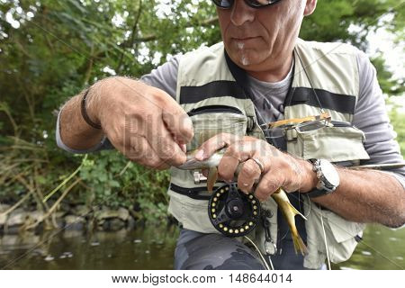 Fly-fisherman taking hook out from trout
