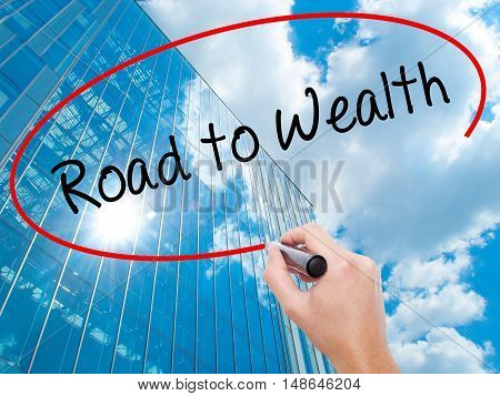 Man Hand Writing Road To Wealth With Black Marker On Visual Screen