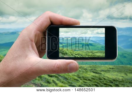 phone in hand man photographing the landscape photos from your phone, Selfie, photographing on the phone, the man photographs the mountain landscape on the phone smartphone side view. carpathians
