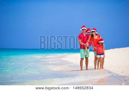 Happy family of four in Christmas Hats during tropical vacation