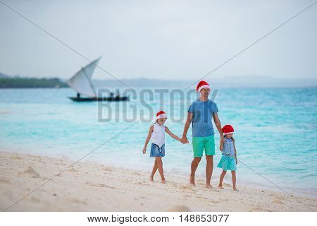 Young father and little girls in Santa hat at tropical beach