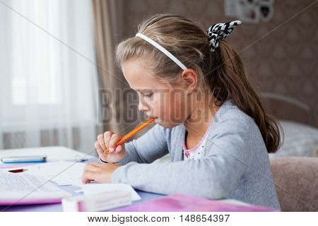Close up little school girl doing homework sitting with a pencil at the table