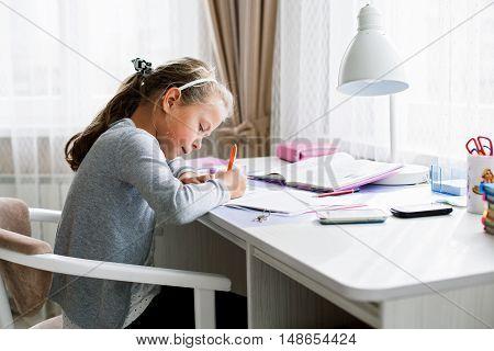 Little school girl writing something in an exercise book doing homework